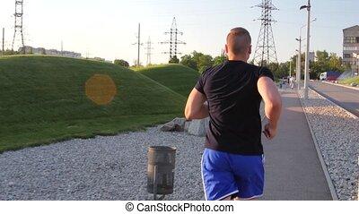 Runner men running in park exercising outdoors fitness tracker wearable technology