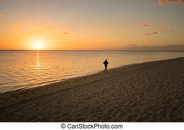 Runner on the beach at sunset
