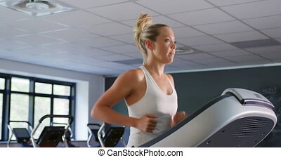 Runner on treadmill - Side view of a young Caucasian woman ...
