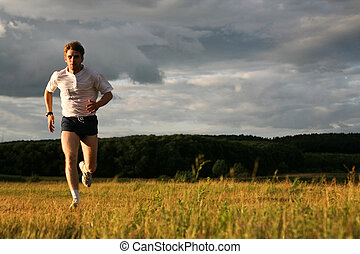 Runner - View of energetic man running in the forest
