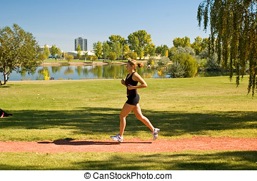 Runner - Young woman jogging through the park.