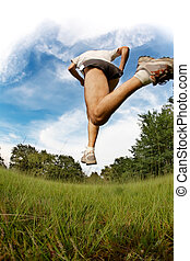 Runner - Male runner jumping and running on meadow against...
