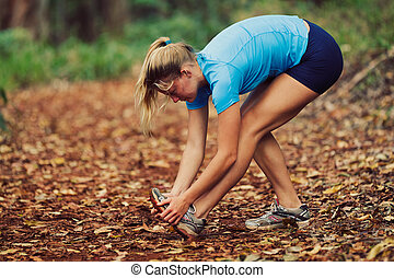 Runner Stretching - Young Woman Stretching after workout Run
