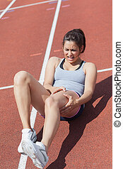 Runner suffering from leg cramp on the track