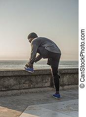 Runner ties shoe by wall near ocean