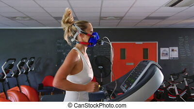 Runner using metabolic gas analyser - Side view of a young ...