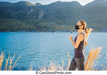 Runner wearing medical mask, Coronavirus pandemic Covid-19. Sport, Active life in quarantine surgical sterilizing face mask protection. Outdoor run on athletics track in Corona Outbreak. Keep your shape during quarantine, pandemic. Young attractive guy in a black medical mask prepares for a jogging ...
