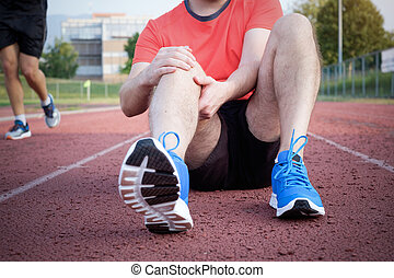 Runner with injured knee on track