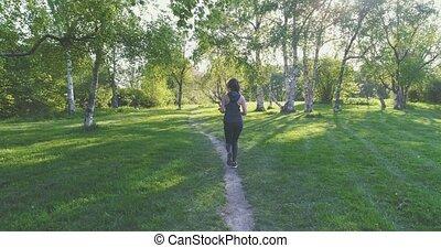 Runner woman dressed in sportwear running in park