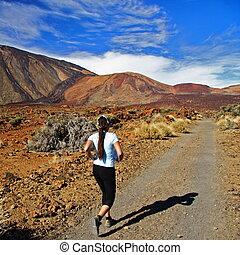 Runner, Woman running on dirt road in amazing volcano ...
