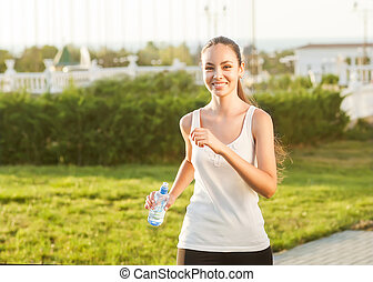 runner - woman running outdoors training for marathon run. Beautiful fit asian fitness model in her 20s. Holds water