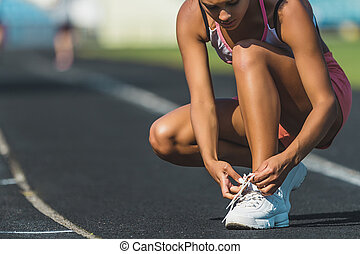 Runner women tying running shoes laces getting ready for race on run track in stadium
