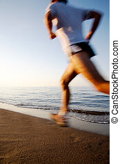 Runner - Young male runner running on a empty beach at dawn...
