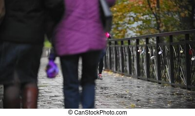 Runner young woman running in autumn park exercising outdoors at rain, pink training suit, slow motion, next to the passers-by, telephoto