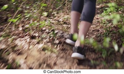 Runner's feet in sports shoes run on forest ground