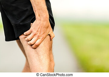 Runner holding sore leg, pain from running or exercising, jogging injury or cramp, cross country in summer nature
