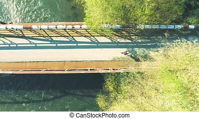 Runners on rusty bridge above the river . Aerial view. -...