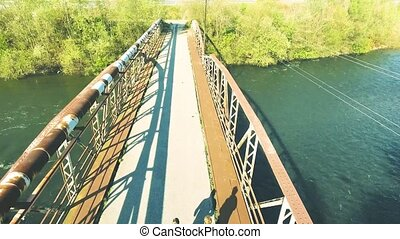 Runners on rusty bridge leading across the river . Aerial...