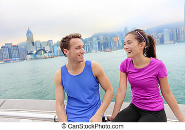 Runners relaxing after workout in Hong Kong city. Running caucasian and asian man and woman post run taking a break talking together on the Avenue of the Stars in Victoria harbor, Hong Kong Skyline.