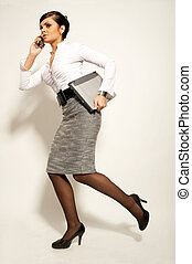 running atractive brunet businesswoman with laptop and phone