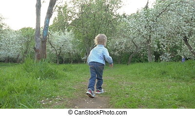 Steadicam slow motion shot of a little boy running along the path in the park, camera is following him.