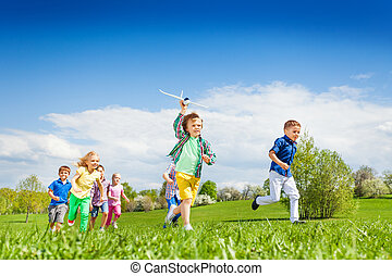 Running boy with airplane toy and other children