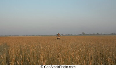Running camera adult cheerful man on a wheat field. Farmer...