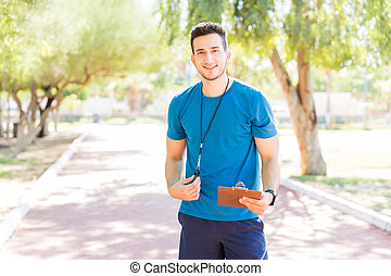 Running Coach Holding Clipboard And Whistle On Footpath In Park