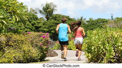 Running couple jogging on park path exercising on beautiful summer day