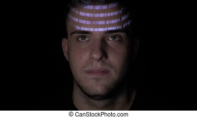Running digital binary data code reflected on the face of a young man working on computer in the dark