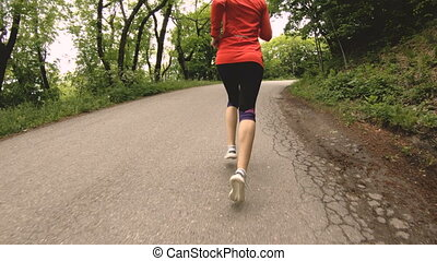 Running girl. Blonde girl doing outdoor sports in the summer forest. Rear view slow-motion wide angle. Close-up of a girl's legs