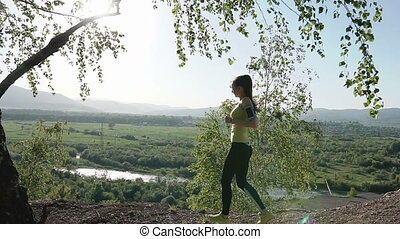 Running - girl runner jogging on forest path in mountains. Fit caucasian female sport fitness model athlete trail running training for cross country race. Athletic running girl at sunset in the mountains