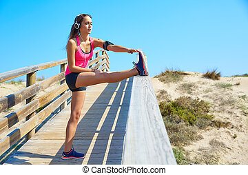 running girl stretching in a beach track with headphores