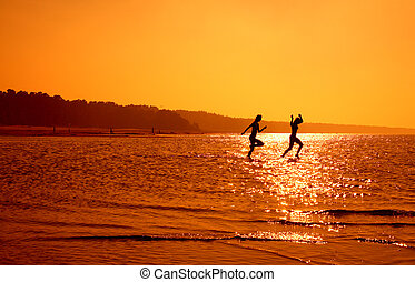 running girls - silhouette image of two running girls in...