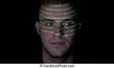 Running green programming code reflected on the face of a...