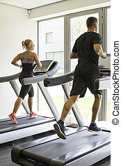 Healthy man and woman running on a treadmill in a gym