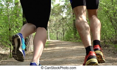 Rear view of two pairs of legs jogging outdoors in slow motion