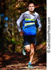 Running in the autumn forest athletic preparation for marathon