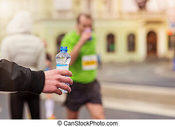 Running in the city - Runners taking a water bottle at the...