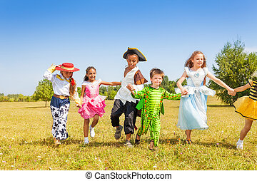 Running kids wearing costumes outside in field