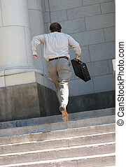 running late - rear view of full body businessman carrying...