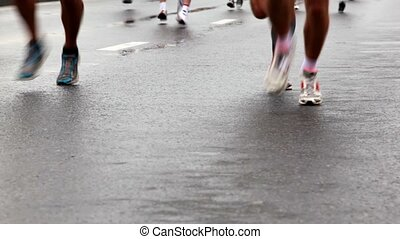 Running legs in sport wear and jogging shoes on wet asphalt at XXX Moscow International Peace Marathon