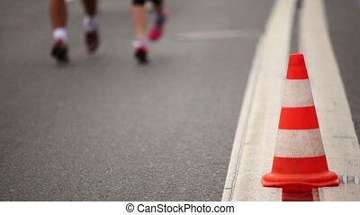 Running legs in sport wear and jogging shoes near cone on asphalt