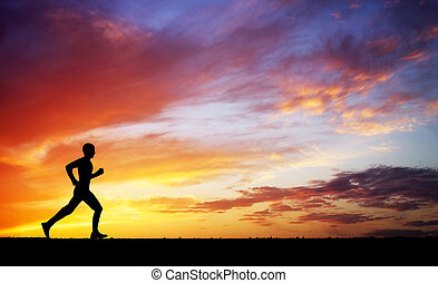 Running man against the colorful sunset sky.
