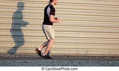 Running man athlete training outdoors exercising on road at sunset