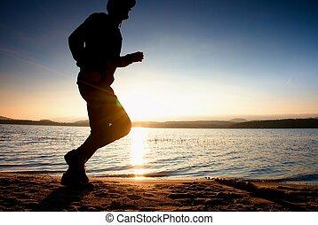 Running man on beach. Sportsman run in baseball cap, jogging guy during the sunrise
