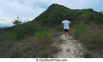 Running man on mountain road. Sport fitness boy exercising outside in mountain. Living healthy lifestyle enjoying outdoor activity.