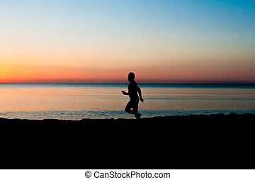 running man on the beach at sunrise