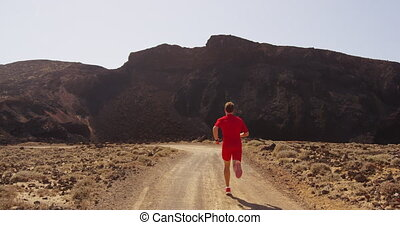 Runner running on sprinting fast on desert road in compression running clothing. Fit man trail running in amazing desert nature landscape. RED EPIC SLOW MOTION