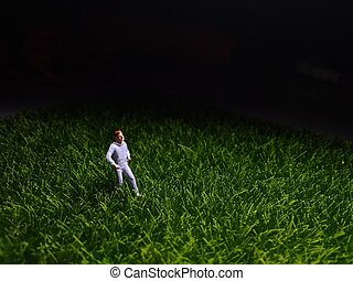 Running Mini Figure man in the night at fresg green grass